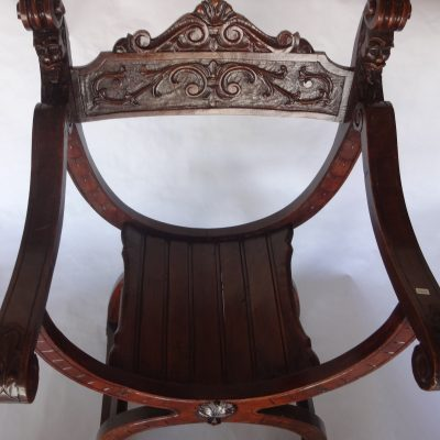 Old hand-carved oak window chair with scrolling arms and grotesque faces