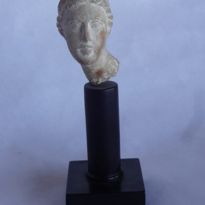 "Small hand-carved stone figure of a woman's head, possibly Greek, labelled on bottom ""Grecian - 200 BC"""