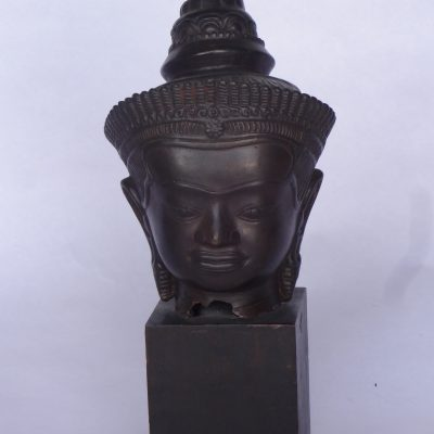 Antique hand-sculpted bronze Thai-style Buddha head, on wooden cube base.