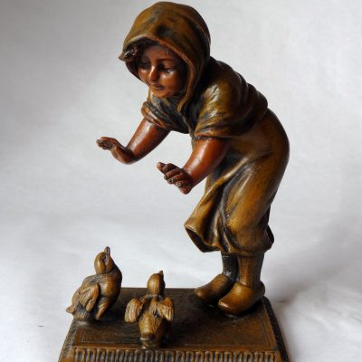 Cast speltre metal figure of a child feeding two birds, unsigned.
