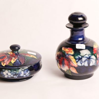 "15   Moorcroft Pottery powder bottle with stopper and  covered  bowl. Orchid and Spring  Pattern. Dark blue ground.  5.5"" H. Two pieces.  English.  Early 20th Century."