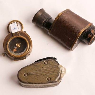 6   Military items.  Hand      generated light (Phillips  Co.); single lens binocular;  brass compass (marked E.Hoehn  - 1917). Three pieces.