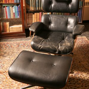 27.  Mid-century bentwood Eames chair and footstool (torn upholstery). Two pieces.