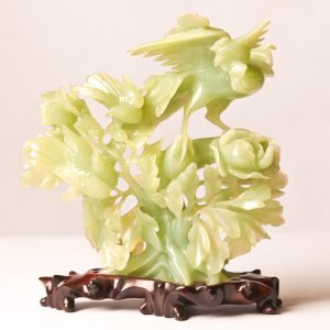 """8.  Chinese serpentine jade carving. Near Celadon colouring, depicting birds on a bush. 7""""H. Mid 20th century. On wooden base."""