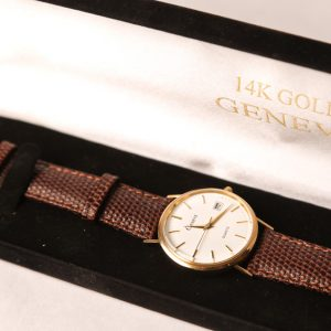 5.  Men's 14kt yellow gold wristwatch. Leather strap. With original $1495.00 price tag still attached. Late 20th century.