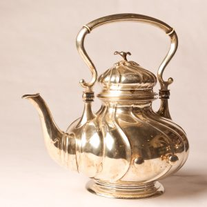 6.  Sterling silver tea pot. Victorian with ivory heat stoppers. With side rests for stand. Late 19th century.