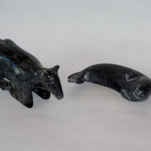 Two Inuit soapstone carvings. Grey grained. Reclined seal signed in syllabics, and kneeling caribou (missing antlers), unsigned.