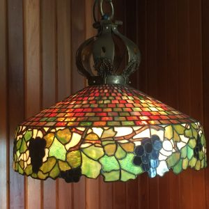50.  Tiffany-quality stained glass chandelier.  Grape and geometric motif. Bronze mounts and chain. Unsigned (originally purchased at auction beside an identical chandelier signed by Tiffany). Early 20th century.
